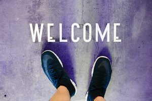 Photo: welcome sign painted on concrete with feet nearby